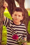 Pojken med rosen begreppet av förälskelsen av barn Arkivbild