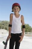 Pojken med skateboarden som ser bort i skridsko, parkerar Fotografering för Bildbyråer