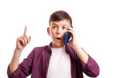 Pojken med telefonen förvånades Royaltyfri Foto