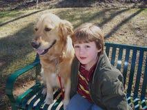 Pojken och den guld- retrieveren tar av planet på royaltyfria bilder