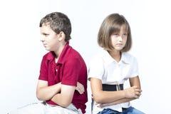 Pojken och en flicka är ilskna på de Arkivbilder