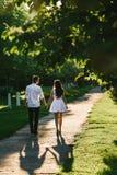 Pojken och en flicka som tillsammans går i en gräsplan, parkerar arkivbild