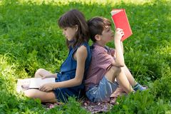 Pojken och flickan är att sitta som är baksida mot baksida på gräsmattan i parkera, och läseböcker Arkivbilder