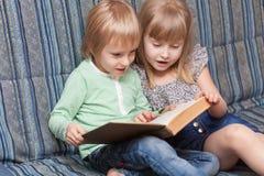 Pojken och flickan är läseboken Arkivfoto