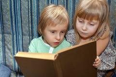 Pojken och flickan är läseboken Arkivfoton