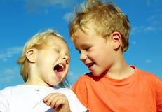 Pojken och flickan är loughen Arkivbild