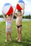 Pojken och flickan för sjö som lite spelar med en uppblåsbar boll arkivbilder