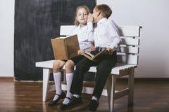 Pojken och flickan från grundskola för barn mellan 5 och 11 årgrupp på den lästa bänken bokar nolla Royaltyfri Bild