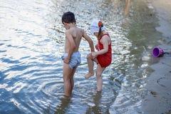 Pojken och flickan går i kalla vattnet Arkivfoton