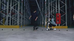 Pojken och flickan gör slalom på rollerblades, och flickan på en sparkcykel knackar ner kottar arkivfilmer