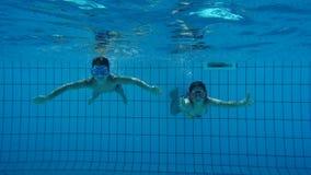 Pojken och flickan i simbassäng simmar undervattens- arkivfilmer
