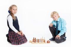 Pojken och flickan i skolalikformign som spelar schack som ser kameran, isolerade vit bakgrund Arkivfoton