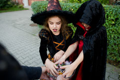 Pojken och flickan i svarta dräkter för allhelgonaafton tar godisar från en vas Arkivfoton