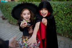 Pojken och flickan i svarta dräkter för allhelgonaafton tar godisar från en vas Royaltyfria Bilder
