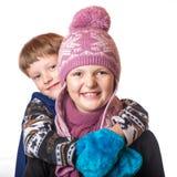 Pojken och flickan i vinterkläder Fotografering för Bildbyråer