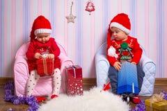 Pojken och flickan kopplar samman i santa hjälpredadräkter Arkivbilder