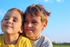 Pojken och flickan ler och ser in mot arkivfoton