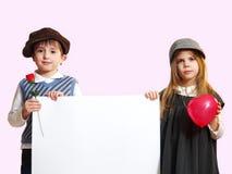 Pojken och flickan med ett vitt ark Fotografering för Bildbyråer
