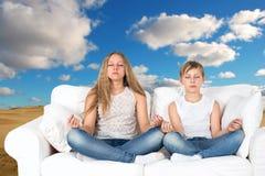 Pojken och flickan mediterar i natur Arkivbild