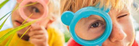 Pojken och flickan ser i ett f?rstoringsglas mot bakgrunden av tr?dg?rden Hem- BANER för skola, LÅNGT FORMAT royaltyfria bilder