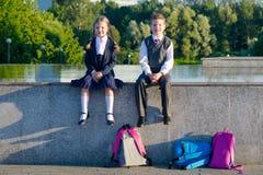 Pojken och flickan sitter tillsammans i parkera efter skola royaltyfri foto