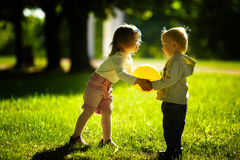 Pojken och flickan som leker med, klumpa ihop sig Arkivbild