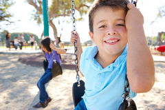 Pojken och flickan som leker på gunga parkerar in Arkivbild