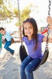 Pojken och flickan som leker på gunga parkerar in Arkivfoton