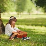 Pojken och flickan som spelar gitarren i sommar, parkerar royaltyfria bilder