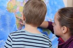 Pojken och flickan spelar i handelsresande royaltyfri foto