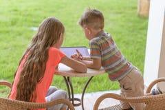 pojken och flickan spelar med minnestavlan arkivbild