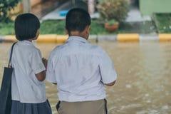 Pojken och flickan väntar för att korsa den översvämmade gatan i tungt häftigt regn är arkivbild