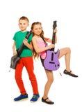 Pojken och flickan vaggar tillsammans att spela på gitarrer Royaltyfri Foto