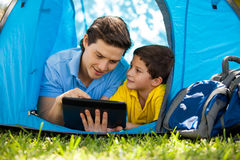 Pojken och hans farsa på campa snubblar Arkivbild