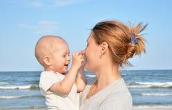 Pojken och hans fostrar gyckel på stranden Fotografering för Bildbyråer