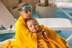 Pojken och hans gulligt behandla som ett barn le brodern efter dusch i simbassäng Royaltyfri Fotografi