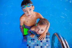 Pojken och hans gulligt behandla som ett barn le brodern efter dusch i simbassäng Arkivfoton