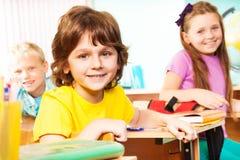 Pojken och hans klasskompisar ser raka, sitter på skrivbord Royaltyfria Bilder