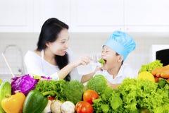 Pojken och hans moder äter sallad Arkivfoton