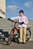 Pojken och hans röda cykel Royaltyfri Fotografi