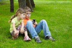 Pojken och hans syster sitter och play den elektroniska leken Royaltyfri Fotografi