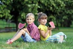 Pojken och lilla flickan äter vattenmelon Fotografering för Bildbyråer