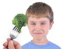 Pojken och sund broccoli bantar på vit Arkivfoto