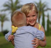 Pojken omfamnar en flicka Royaltyfri Foto