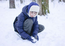 Pojken omkring som ska kastas, kastar snöboll Fotografering för Bildbyråer