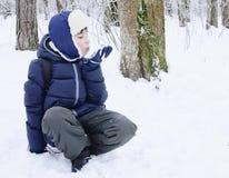 Pojken omkring som ska kastas, kastar snöboll Arkivfoto