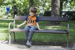 Pojken på bänk parkerar in Arkivfoton