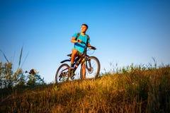 Pojken på cykeln och solnedgång Fotografering för Bildbyråer
