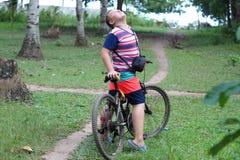 Pojken på cykeln ser upp royaltyfri fotografi