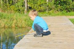 Pojken på en träbro spelas med en pinne i vattnet _ arkivfoton